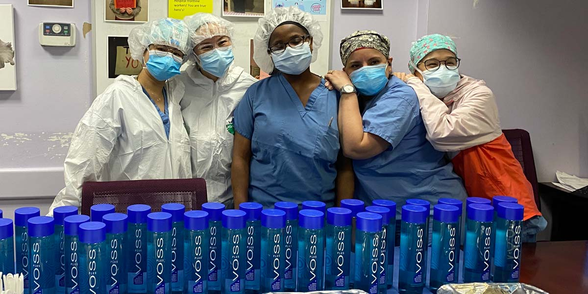 Hospital staff holding bottles of VOSS Water